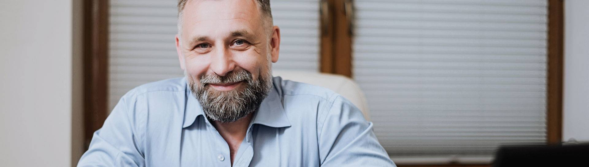 Middle age man with grey beard smiling in office setting