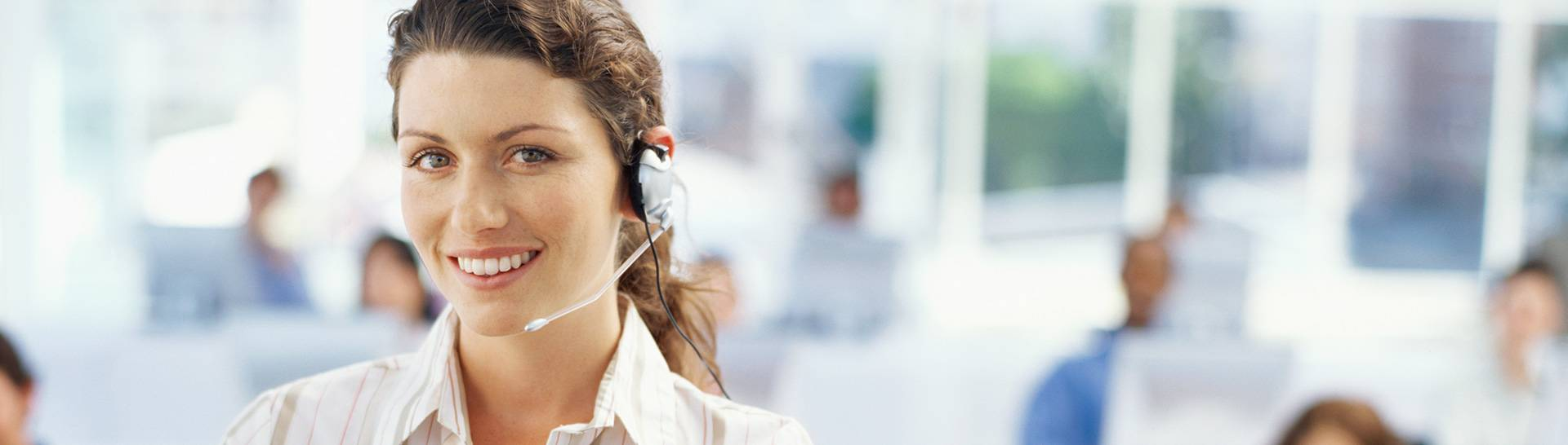 Woman with green eyes and ponytail and headset with call center in background - natural light office building