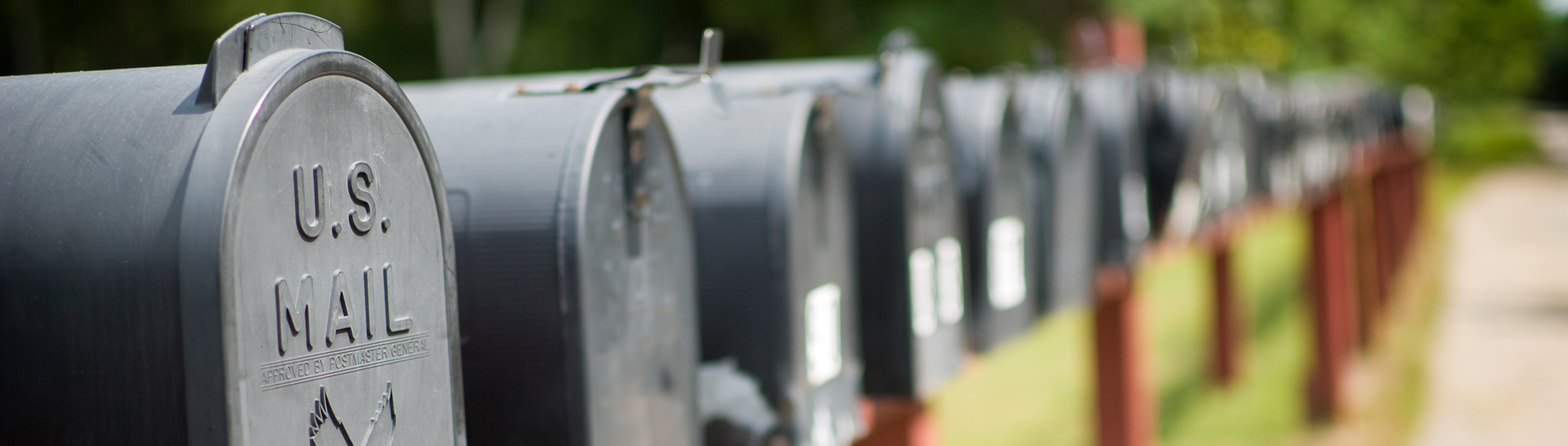 Row of black mailboxes outside on street